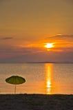 Sunshade on a sandy beach at sunset Stock Photography