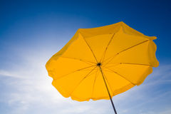 Sunshade in the sky. A yellow sunshade against a deep blue sky stock image