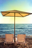 Sunshades and chaise lounges on beach. Summer seascape. Beautiful seaview royalty free stock image