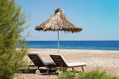 Sunshades and chaise lounges on beach. Summer seascape. Selective focus royalty free stock images