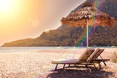 Sunshades and chaise lounges on beach. Summer seascape. Tinted toned coloration image. Selective focus royalty free stock photography
