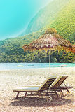 Sunshades and chaise lounges on beach. Summer seascape. Tinted toned image. Selective focus royalty free stock photo