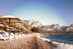 Sunshades and chaise lounges on beach. Summer seascape. Sunshades and chaise lounges on beach. Turkey, Kemer. Beautiful view of mountains and sea stock image