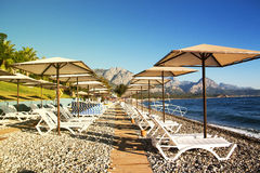 Sunshades and chaise lounges on beach. Summer seascape. Sunshades and chaise lounges on beach. Turkey, Kemer. Beautiful view of mountains and sea royalty free stock photography
