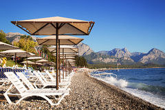 Sunshades and chaise lounges on beach. Summer seascape. Sunshades and chaise lounges on beach. Turkey, Kemer. Beautiful view of mountains and sea stock photo