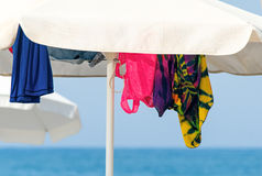 Sunshades and clothes on a sea beach Royalty Free Stock Photography