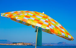 Sunshades and clothes on a sea beach Royalty Free Stock Photo