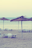 Sunshades on empty beach during sunrise. Royalty Free Stock Photography
