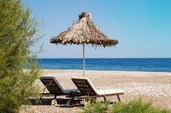 Sunshades i bryczka hole na plaży błękitny skał denny seascape nieba lato Obrazy Royalty Free