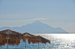 Sunshades made from palm branches, aegean sea and a Holy mountain Athos in background Royalty Free Stock Image