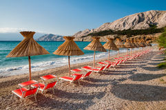 Sunshades and orange deck chairs on beach at Baska - Croatia. Sunshades and orange deck chairs on beach at Baska - Krk - Croatia stock image