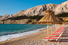 Sunshades and orange deck chairs on beach at Baska - Krk Royalty Free Stock Photos