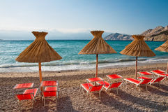 Sunshades and orange deck chairs on beach at Baska - Krk - Croat Royalty Free Stock Images