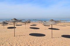 Sunshades throwing circular shadows on the beach Stock Images