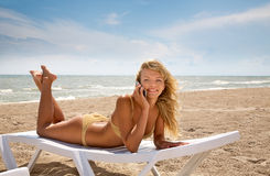 Sunshine. Landscape with  the beautiful happy girl, talking  on phone on a  sea coast Stock Image