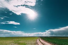 Sunshine Above Spring Rural Meadow Field And Country Open Road. Royalty Free Stock Images