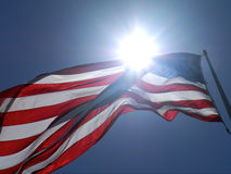 Sunshine and American flag. Low angle view of American flag with sun shining in background Royalty Free Stock Photos