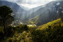 Sunshine between clouds, mountain panorama. Sunshine appearing from clouds in a mountain meadow panorama view Royalty Free Stock Photos