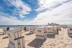Sunshine on the beach. A sandy beach with beach chairs in the sunshine and in the background the historic pier of Ahlbeck Royalty Free Stock Photos