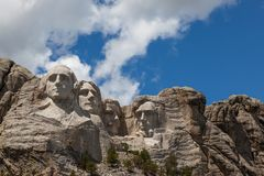 Mount Rushmore in Sunshine. Sunshine, blue sky and white clouds provide a striking back drop for the carved faces of four famous United States Presidents in royalty free stock photo