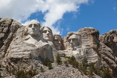 Mount Rushmore in Sunshine. Sunshine, blue sky and white clouds provide a striking back drop for the carved faces of four famous United States Presidents in stock photo