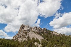 Mount Rushmore in Sunshine. Sunshine, blue sky and white clouds provide a striking back drop for the carved faces of four famous United States Presidents in stock photography