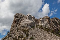 Mount Rushmore in Sunshine. Sunshine, blue sky and white clouds provide a striking back drop for the carved faces of four famous United States Presidents in royalty free stock image