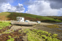 Sunshine on boat wrecks. Sun shines on the peeling paint of two old abandoned wooden boat wrecks on the shore of Loch Harport on Isle of Skye Scotland Stock Photos