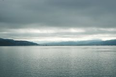Sunshine breaking through a stormy sky to fall on a silver lake. Grey clouds hover over a still lake. The water looks silver. Hills are in the distance, and Royalty Free Stock Image