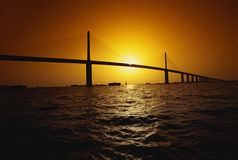 Sunshine Bridge over ocean, FL. This is the Sunshine Bridge at sunset. It is one of the longest suspension bridges in North America. The ocean is shown in the Royalty Free Stock Images