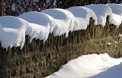 Sunshine and cap of fresh snow define a stone wall Stock Photos
