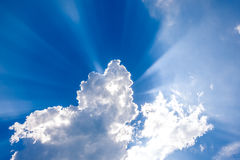 Sunshine through the clouds. In the blue sky background Royalty Free Stock Photography