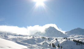 Sunshine on clouds rolling over a snowy mountain. Royalty Free Stock Photography