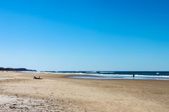 Sunshine Coast beach in Australia with unreognizable people silhouetted in the distance, including one man on a laptop stock images