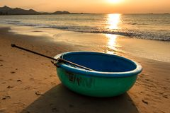 Seascape with Sunshine on A Coracle - Traditional Vietnamese Fishing Boat on Sandy Beach at Sunrise stock photo
