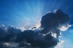 Sunshine through the dark clouds from ant view. Blue sky background and sun ray light down Stock Photo