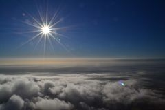 Sunshine directly above the clouds stock photo