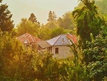 Sunshine Filtering Through Rain, Greek Mountain Village Houses. A rainy evening in a Greek mountain village, with golden sunlight filtering through rain and fog Stock Photo