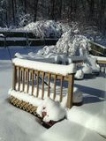 Sunshine highlights snow on backyard deck and steps. Following an overnight snowfall, fluffy pristine snow is mounded on deck and steps Stock Photo
