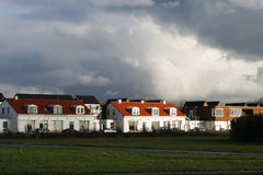 Sunshine on houses under a thunder sky Stock Photo