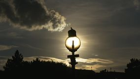 Sunshine inside a streetlamp. Sun seen through street lamp with gorgeous sunset sky and clouds. Cityscape with backlight. Solar energy stock footage