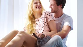 Sunshine on lovely couple in sleep wear sitting on floor with domestic rabbit. Near big curtained window. young man and woman spend leisure time with their pet stock footage