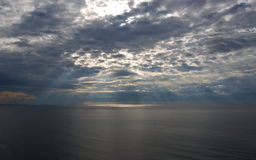 Sunshine make the way through clouds over a sea surface. Royalty Free Stock Image