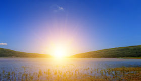 Sunshine on mountain and blue sky over river. Royalty Free Stock Photo