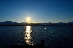 Sunshine over blue fjord and pier with snowy mountain background. Northern norway Royalty Free Stock Photography