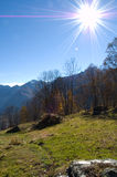 Sunshine over mountainside. Scenic view of bright sunshine and rays in blue sky over wooded hillside with mountain range in background Royalty Free Stock Photo