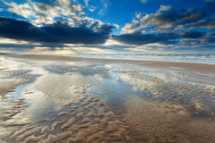 Sunshine over North sea beach at low tide Stock Photos