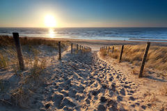 Sunshine over path to beach in North sea Stock Photos