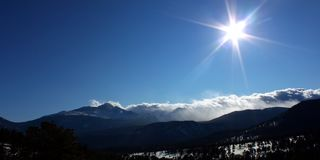 Sunshine over Rocky Mountains. Bright sunshine over a snow covered landscape of Rocky Mountain National Park Stock Photos