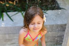 Sunshine portrait drops of water fall on little girl closing eye royalty free stock photo